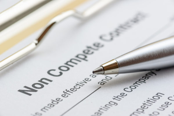 non compete agreement on a clipboard with a silver pen on top
