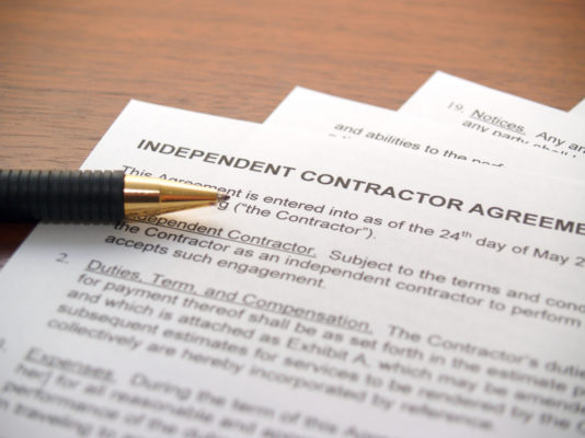 pen resting on a copy of an independent contractor agreement