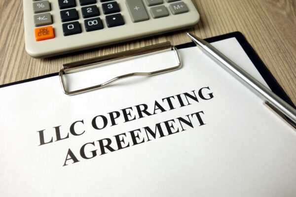 """clipboard holding a sheet of paper that says """"LLC Operating Agreement"""""""